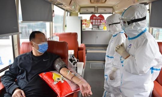 Пациент в маске и врачи в защитных костюмах